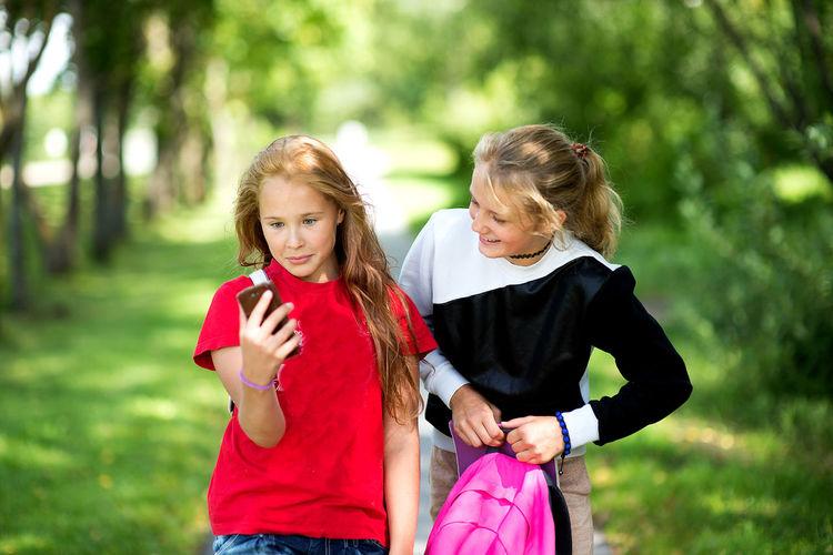 Friends Taking Selfie Through Mobile Phone In Park