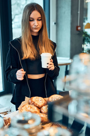Young woman holding coffee cup on table