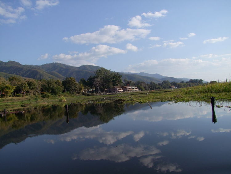 Mountain Range on edge of Inle Lake Beauty In Nature Blue Sky White Clouds Composition Glassy Water Inle Lake Lake Landscape Mountain Mountain Range Myanmar Natural Beauty Nature No People Outdoor Photography Reflection Lake Reflections In The Water Scenics Sunlight And Shadows Tourism Tourist Attraction  Tranquil Scene Tranquility Travel Destination Tree Water