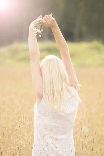 One Person Land Women Hair Adult Arms Raised Field Blond Hair Real People Hairstyle Long Hair Human Arm Leisure Activity Lifestyles Rear View Plant Focus On Foreground Nature Standing Outdoors Beautiful Woman Human Limb