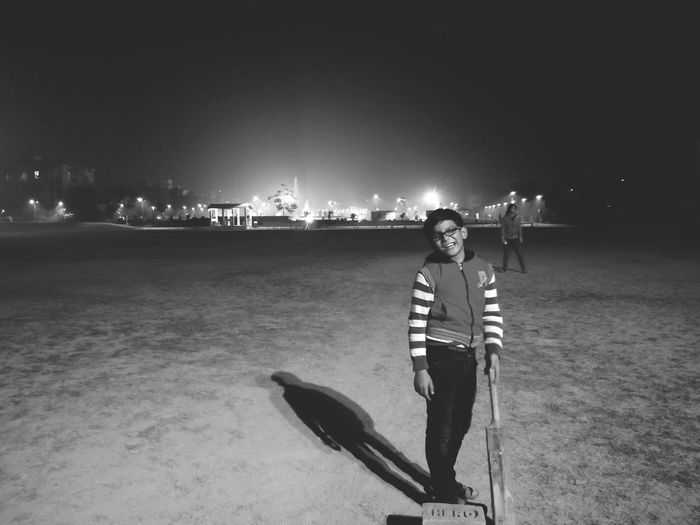 Portrait of smiling boy holding cricket bat while standing on field at night