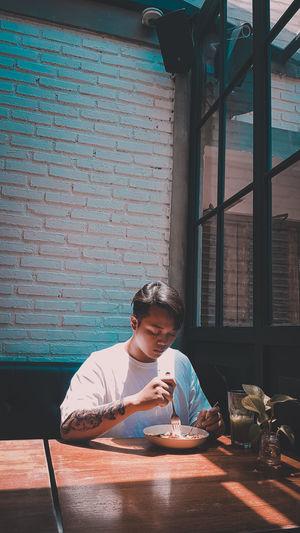 Portrait of boy sitting on table against window