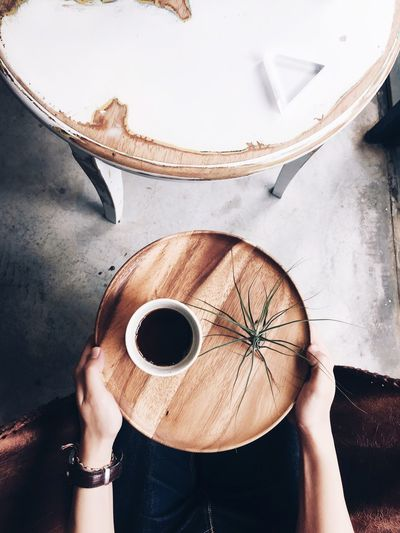 Midsection Of Person Holding Black Coffee In Wooden Tray