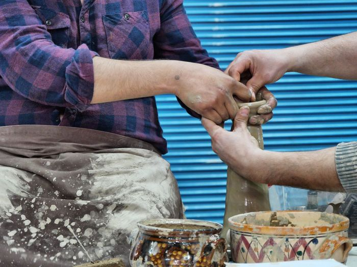 Midsection of man with coworker making earthenware