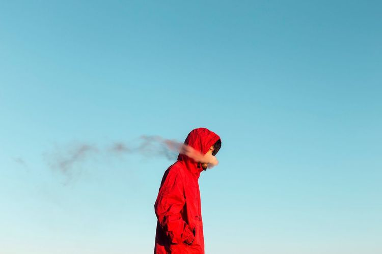 Person with red umbrella standing against blue sky