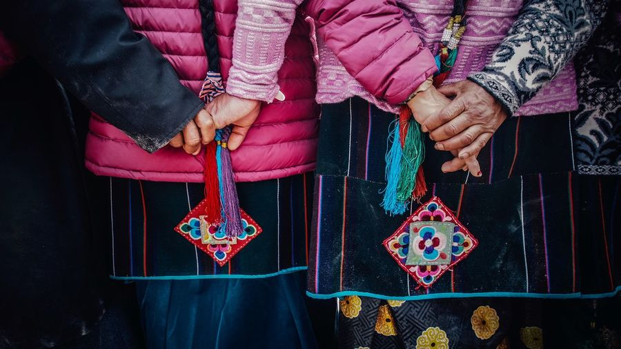 Midsection of women in traditional clothing while holding hands during tibetain new years day