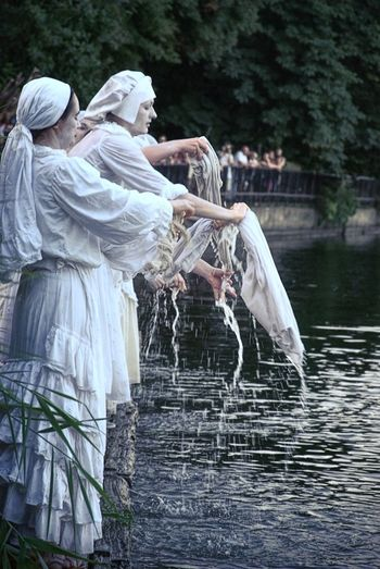 Side View Of Women Washing Clothes At Lake