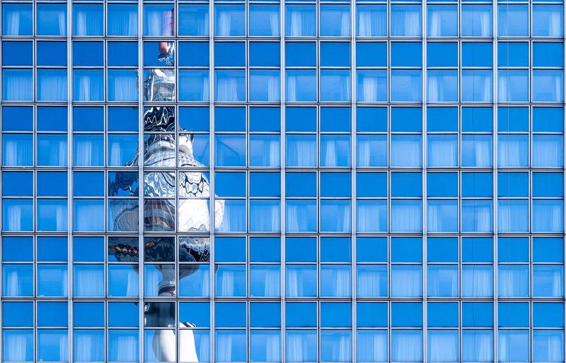 Fernsehturm reflecting on modern glass building