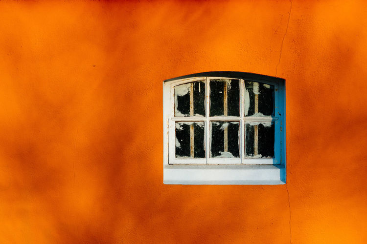 Close-up of abandoned window on orange wall