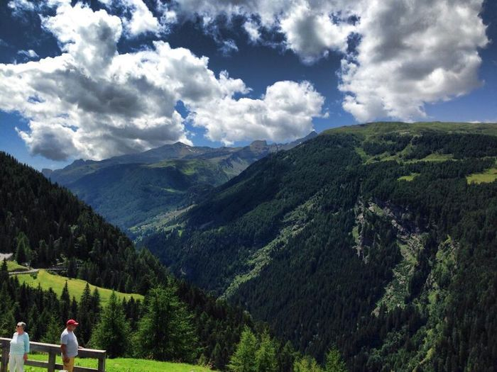 Panoramic shot of people on landscape against sky