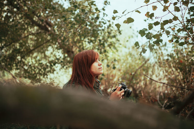 Young woman using mobile phone in tree