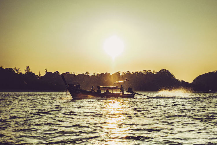 Beauty In Nature Boat Clear Sky Longtail Boat Men Mode Of Transport Nature Nautical Vessel One Person Outdoors Real People Sailing Scenics Sea Silhouette Sky Sun Sunbeam Sunlight Sunset Tranquility Transportation Tree Water Waterfront