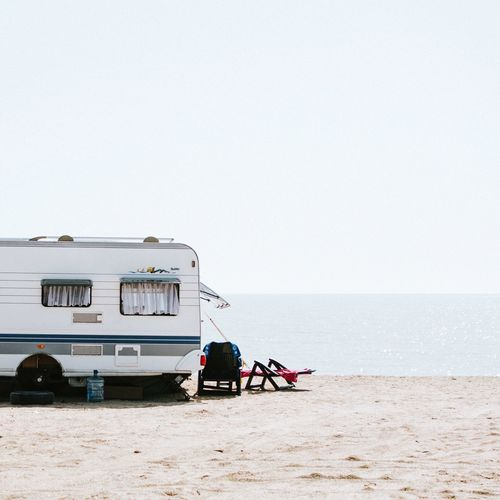 Caravan on beach against clear sky