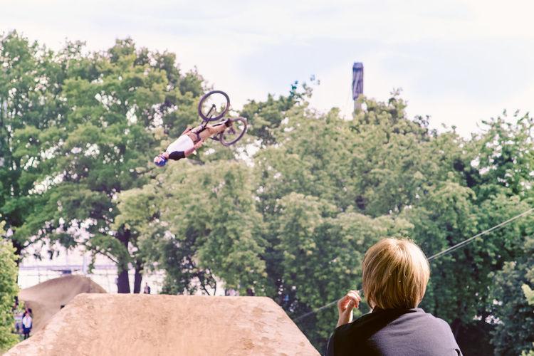Man Looking At Bicycle Stunt Against Tree