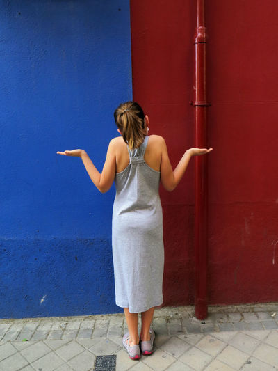 Rear view of girl standing by wall