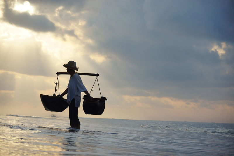 Man carrying baskets while standing in sea against sky during sunset