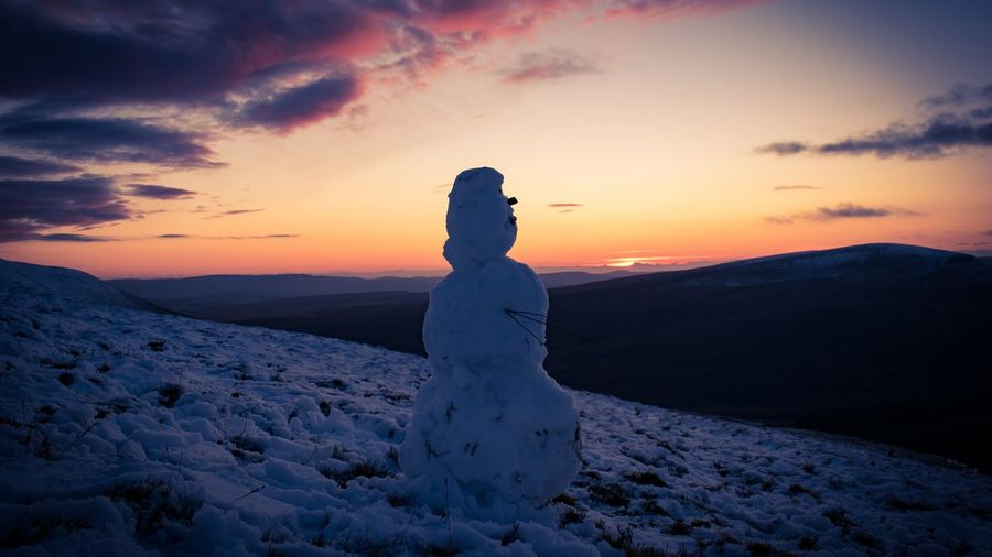 Snowman standing on snow covered land during sunset