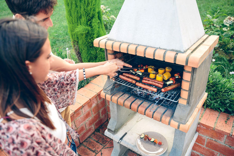 Young Couple Preparing Food On Barbecue