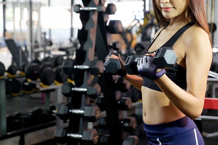 Muscular building woman workout with dumbbell in sport gym. ASIA Adult Body Conscious Dumbbell Effort Equipment Exercise Equipment Exercising Fitness Fitness Training Fitnessmodel Gym Gym Time Healthy Lifestyle Indoors  Lifestyles Muscular Build One Person Sport Sports Training Strength Weight Weight Training  Weights Women
