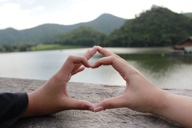 Cropped image of man and woman making heart shape by lake
