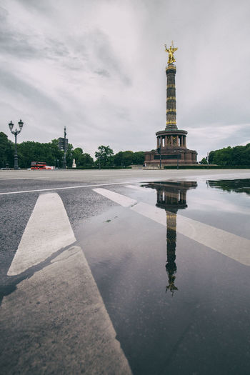Reflection Of Built Monument Against Clouds