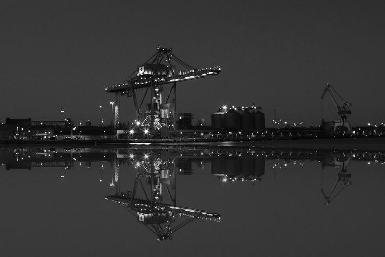 Harbor cranes reflecting in water
