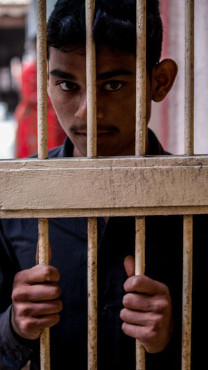 Portrait of teenage boy standing behind prison bars
