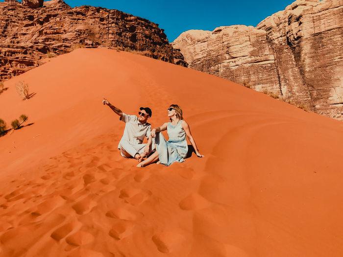 People on rock in desert against sky