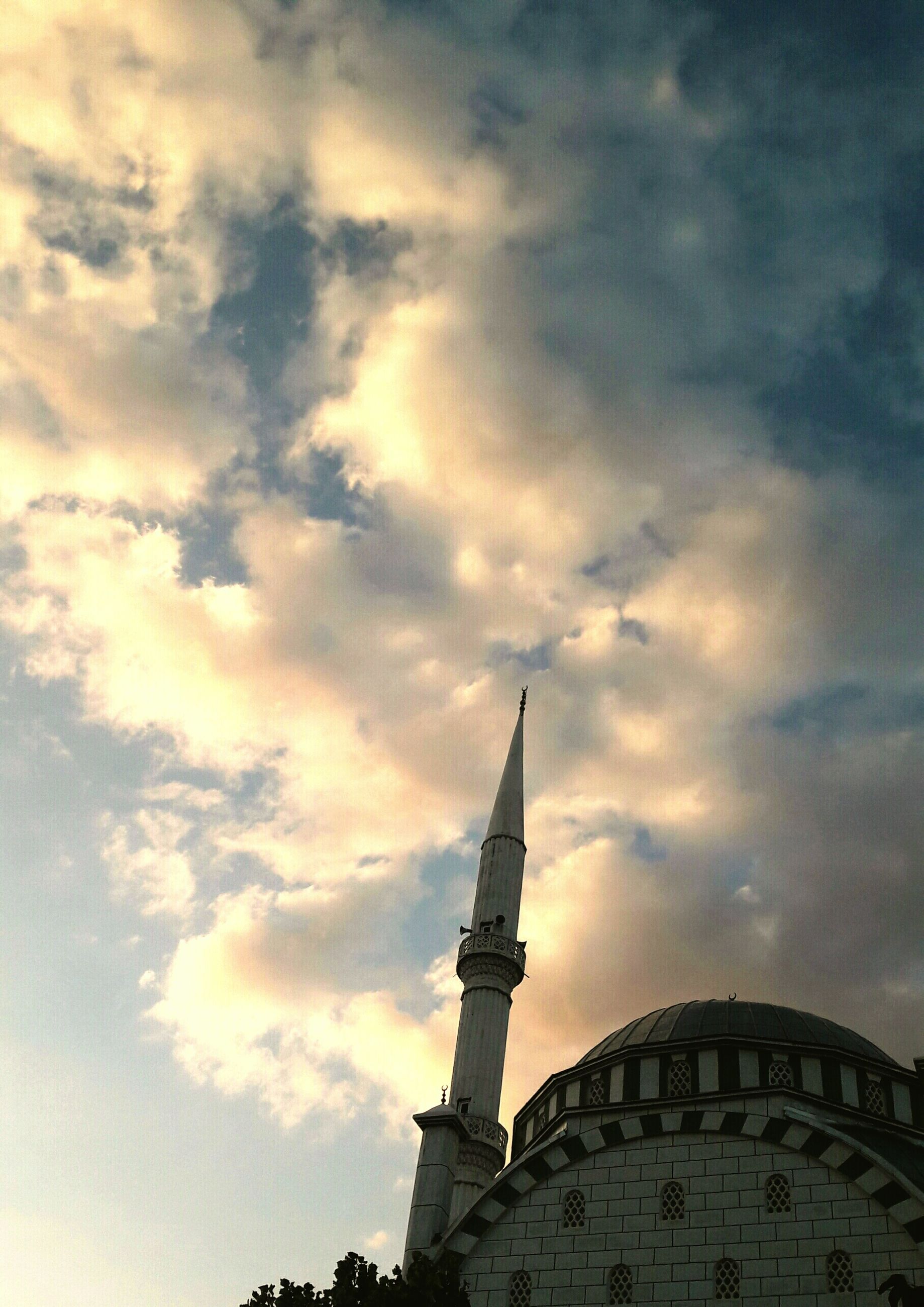 low angle view, architecture, sky, built structure, cloud - sky, building exterior, cloudy, cloud, tower, high section, famous place, travel destinations, outdoors, religion, place of worship, international landmark, travel, no people, sunset, tall - high