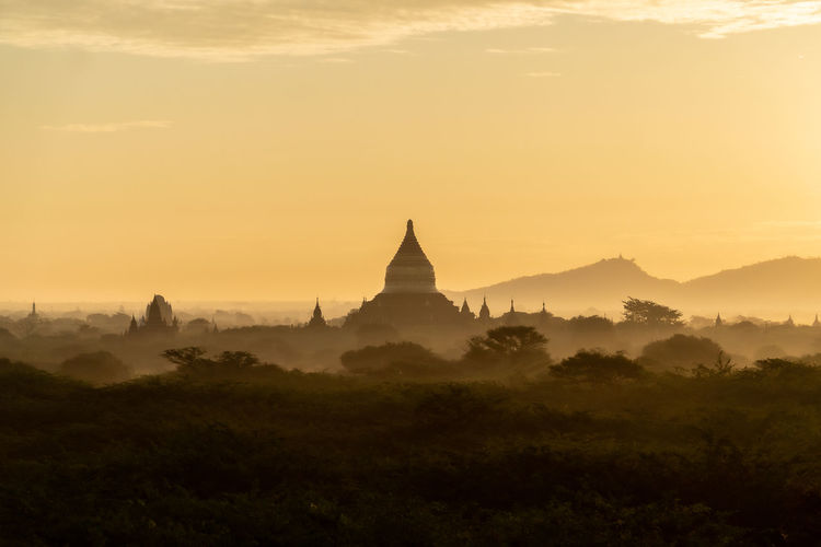 View of pagoda against sky during sunrise