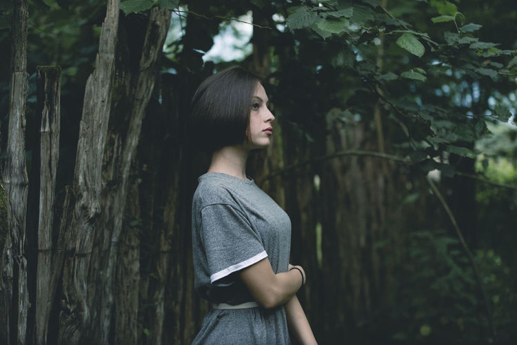 Side view of woman looking away in forest