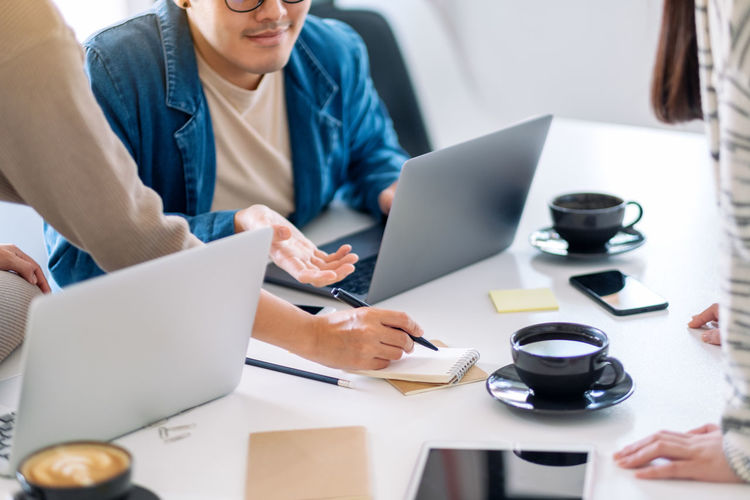 Midsection of colleagues with laptops working at office desk