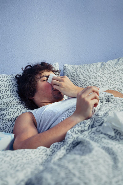 Portrait of young man sneezing and covering nose with tissue while holding thermometer lying on bed. Sickness and healthcare concept. Bed Lying Man Medicine Tissue Unhappy Allergy Bedroom Cold Fever Flu Grippe Headache Heat Illness Influenza Male Nasal One Person Real People Sick Sickness Sneezing Temperature Vertical