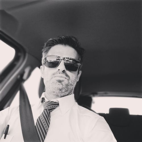 Portrait of man wearing sunglasses in car