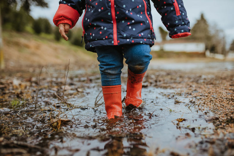 Low section of child standing in puddle