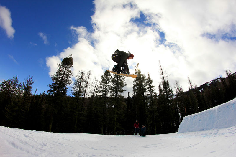 Acrobatics  Action Shot  Cloud Cloud - Sky Cold Temperature Covering Enjoyment Full Length Grabbing Jumping Leisure Activity Lifestyles Low Angle View Men Mountain Nature Season  Sky Snow Snowboard Snowboarding Terrain Park Tree Weather Winter