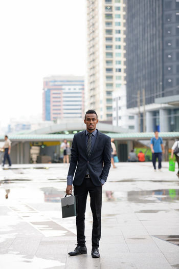 Full length portrait of businessman standing in city