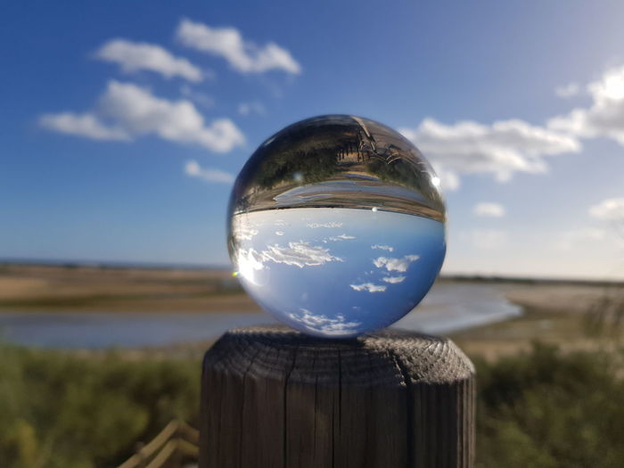 Close-up of crystal ball hanging on glass against sky