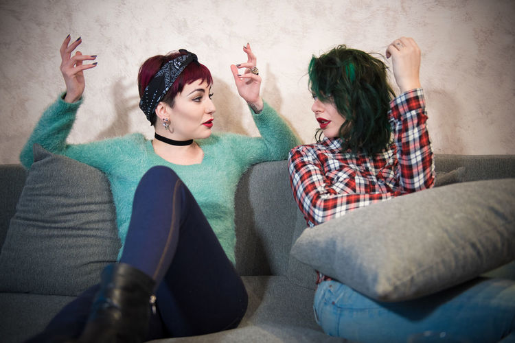 Two young women talking on sofa