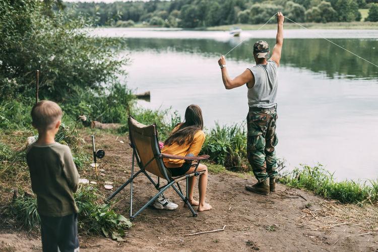 Rear view of men sitting by lake