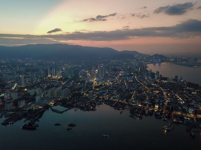 High angle view of illuminated city by sea against sky