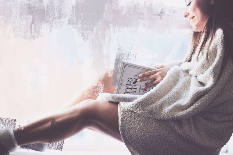 Double Exposure Image Of Smiling Woman Reading Book And Wall
