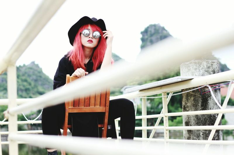 Portrait of young woman wearing sunglasses while sitting on chair by railing