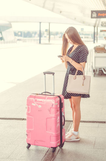 Woman with luggage using mobile phone at airport