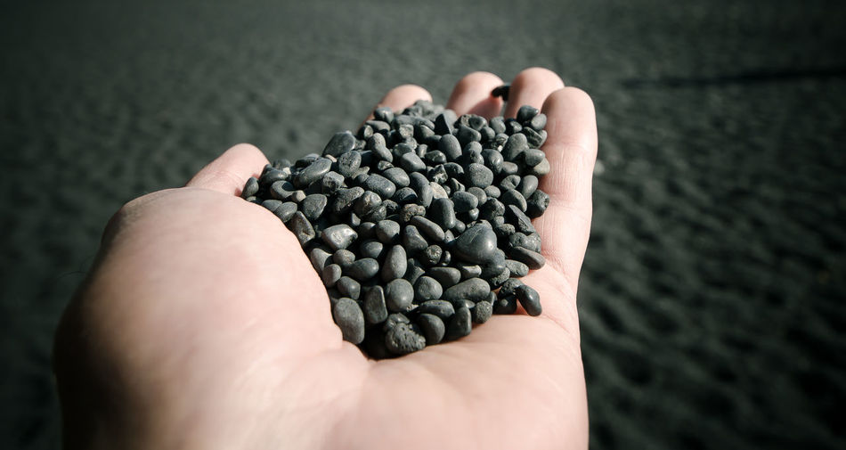 Close-Up Of Human Hand Holding Black Pebbles At Beach