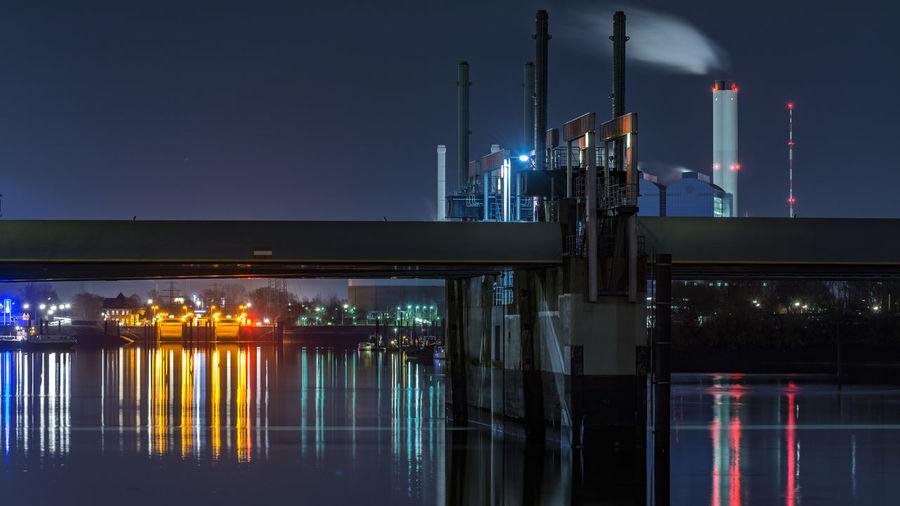 Illuminated harbor by river at night