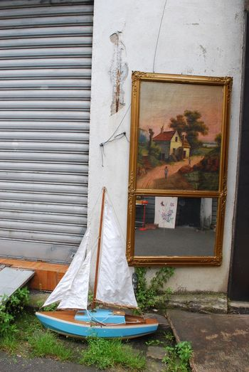 Items on display at a Paris flea market. EyeEmNewHere Architecture Building Exterior Corrigated Steel Fleamarket Outdoors Paintings Sailboat Wall - Building Feature