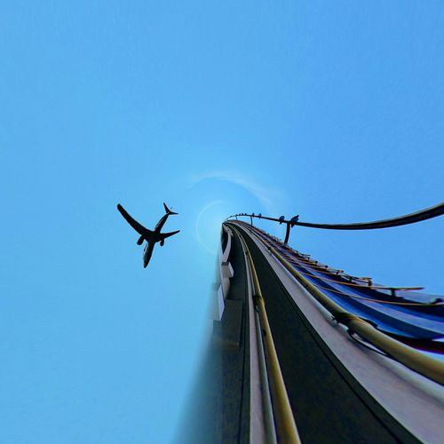 Little Planet Effect Of Airplane And Rollercoaster Against Clear Blue Sky