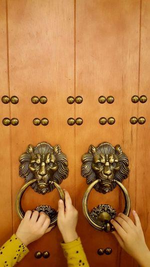 Cropped hands holding metallic door knockers
