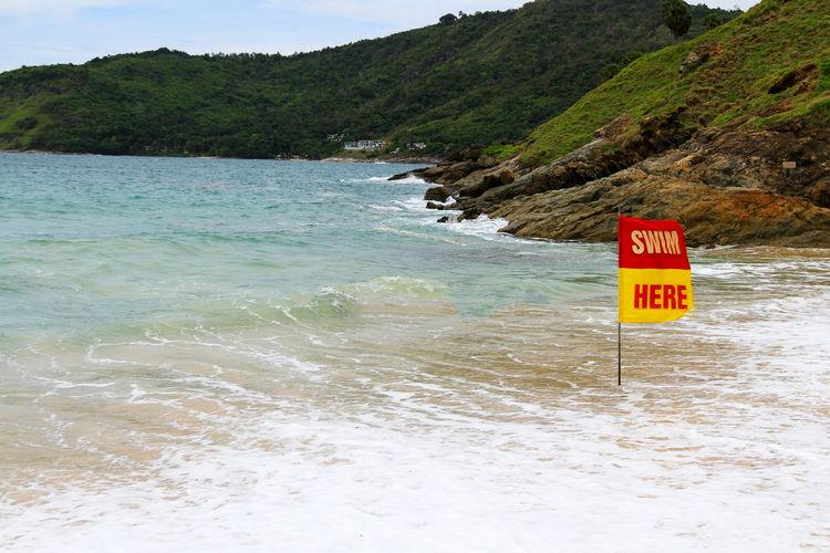 Warning sign on beach against sky